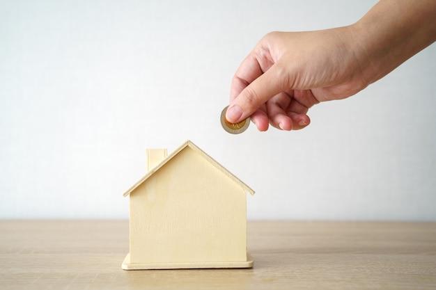 Entreprise mettez la pièce dans la tirelire de style maison pour économiser de l'argent, économiser de l'argent sur les investissements,