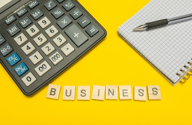Entreprise de mot faite avec des lettres en bois sur une calculatrice jaune et moderne avec un stylo et un cahier.