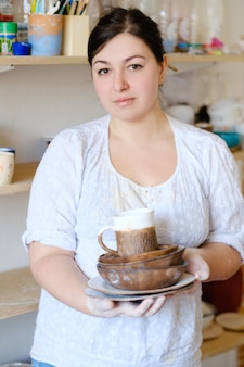Entreprise de poterie. fabrication artisanale artisanale. artisan woman holding assortiment de vaisselle artisanale et plaques d'argile en atelier