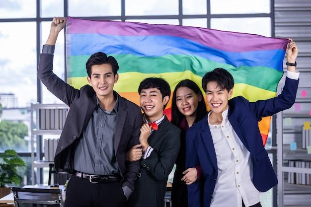 Entreprise prospère avec des travailleurs heureux un groupe d'hommes d'affaires asiatiques de divers genres (lgbt) célèbre la liberté et le soutien lgbt avec le drapeau lgbt dans la salle de réunion du bureau