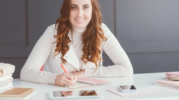 Entreprise de réseau social. marketing en ligne. smm femme sur le lieu de travail prenant des notes dans le calendrier.
