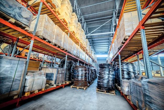 Entreprise de transport et de fret en entrepôt. au premier plan un tas de cartons et une bobine de tube en plastique.