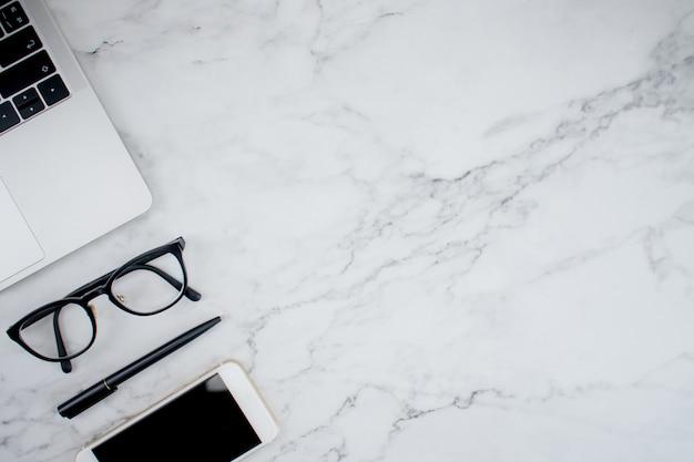 Entreprise travaillant dans un lieu de travail moderne avec des accessoires pour travailler sur une table en marbre.