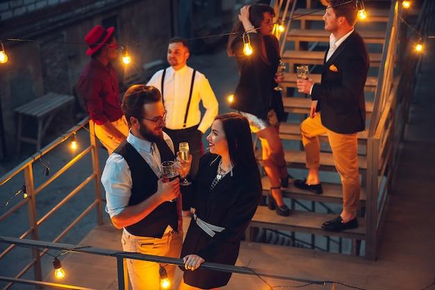 Les entreprises célébrant à la lumière chaleureuse des lampes le soir d'été, les jeunes amis, les collègues ont l'air heureux, parlent, s'amusent. vacances, week-end, affaires et finances, concept d'amitié. construction d'équipe.