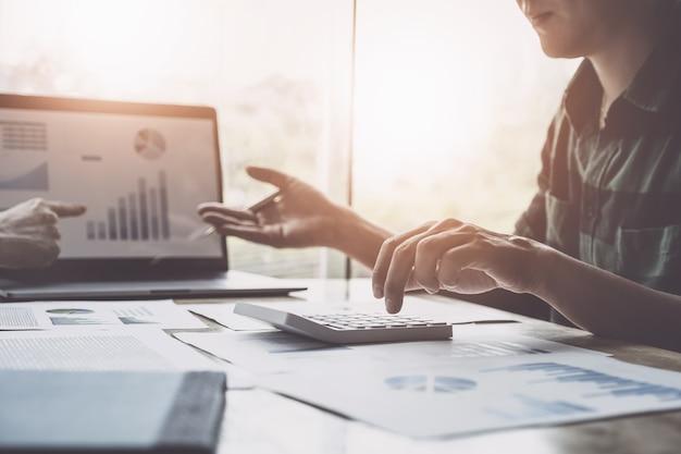 Entreprises et partenariats discutant de l'utilisation d'une calculatrice pour examiner le bilan annuel avec un stylo et d'un ordinateur portable pour calculer le budget. intégrité de l'audit avant le concept d'investissement.