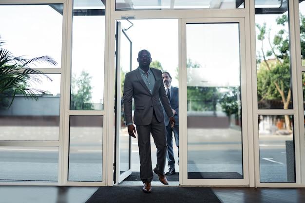 Entrer dans le centre d'affaires. deux hommes d'affaires riches entrant dans le centre d'affaires tout en ayant une réunion importante