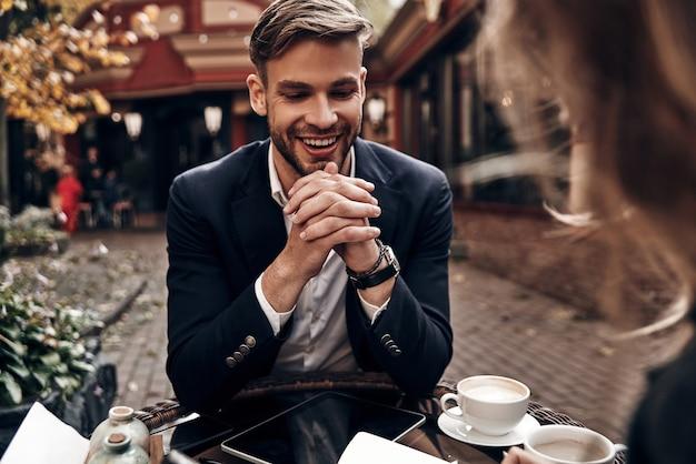 Entretien d'embauche. beau jeune homme en vêtements décontractés intelligents souriant tout en discutant avec une jeune femme au restaurant