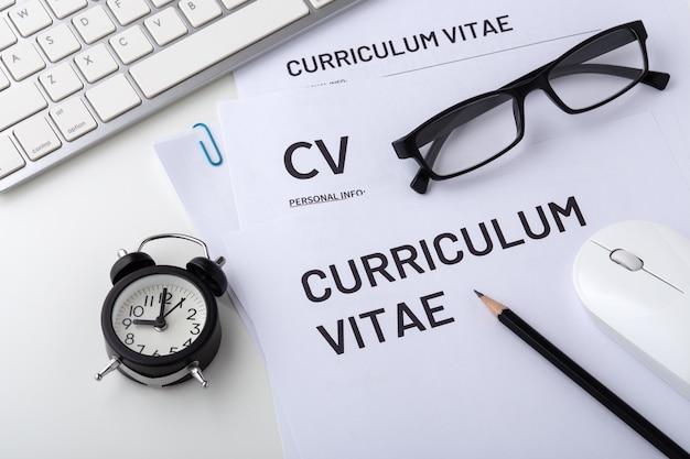 Entretien d'embauche avec cv, horloge sur un bureau blanc