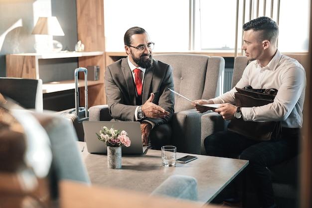 Entretien d'embauche. jeune économiste prometteur se sentant curieux en venant à un entretien d'embauche avec un homme d'affaires célèbre