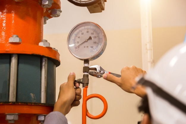 Entretien d'un ingénieur asiatique, vérification des données techniques de l'équipement du système condenseur pompe à eau et manomètre