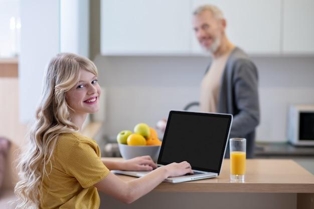 Entretiens du matin. une fille blonde assise dans la cuisine et parlant à son père