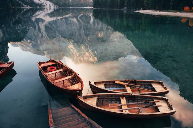 Entrez et nagez. bateaux en bois sur le lac de cristal avec une majestueuse montagne derrière. reflet dans l'eau