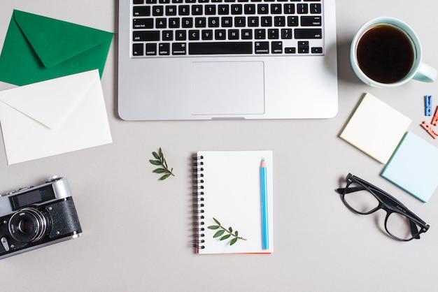 Enveloppe; appareil photo rétro; bloc-notes en spirale; lunettes et ordinateur portable ouvert sur fond blanc