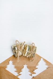 Enveloppe artisanale avec des arbres de noël et des cadeaux