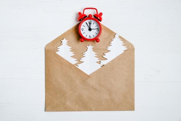 Enveloppe artisanale avec des arbres de noël et une horloge rouge