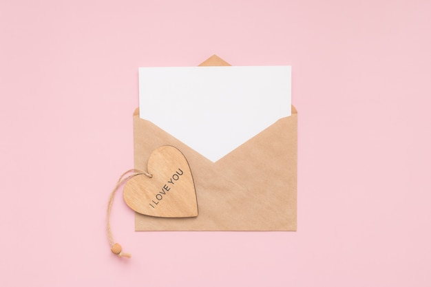 Enveloppe artisanale, carte blanche en papier vierge et coeur en bois avec les mots je t'aime sur un mur rose. place pour le texte. mise à plat. vue de dessus. joyeuse saint valentin.