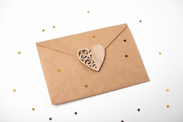 Enveloppe artisanale avec le cœur en bois dessus et de petites étoiles dorées sur blanc. lettre d'amour romantique pour le concept de la saint-valentin.