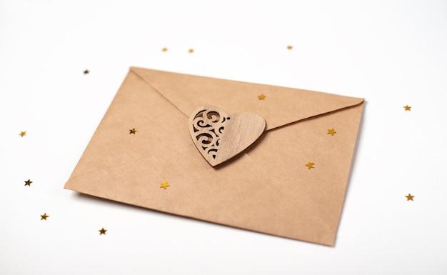Enveloppe artisanale avec coeur en bois et petites étoiles dorées sur fond clair (blanc). lettre d'amour romantique pour le concept de la saint-valentin.