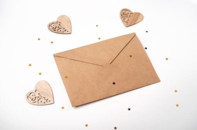 Enveloppe artisanale avec coeurs en bois et petites étoiles dorées sur fond clair (blanc). lettre d'amour romantique pour le concept de la saint-valentin.