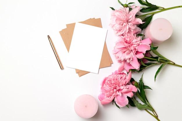 Enveloppe artisanale avec une feuille de papier avec un bouquet de pivoines roses sur fond gris