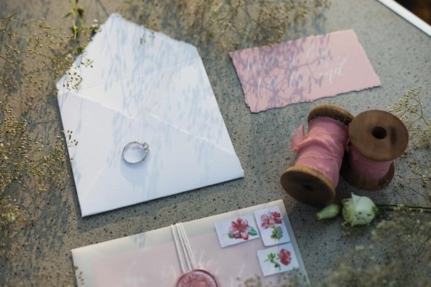 Enveloppe blanche avec une alliance de mariée dessus, bobines de ruban rose