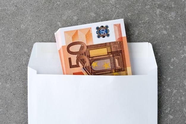 Enveloppe blanche avec billets de 50 euros.