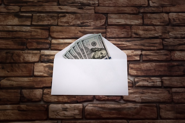 Enveloppe blanche avec billets de cinq cents dollars dans un rayon de lumière contre un mur de briques sombres.