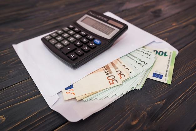 Enveloppe blanche avec billets en euros et calculatrice