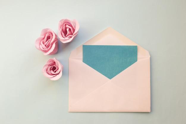 Enveloppe blanche, carte vierge bleue, trois fleurs roses roses sur fond bleu. lay plat minimal
