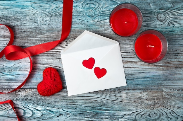 Enveloppe blanche, coeurs rouges, ruban et bougies sur fond gris-bleu en bois.