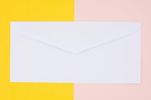 Enveloppe blanche courrier sur fond jaune et rose