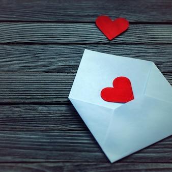 Enveloppe blanche avec deux coeurs en papier rouge sur bois gris