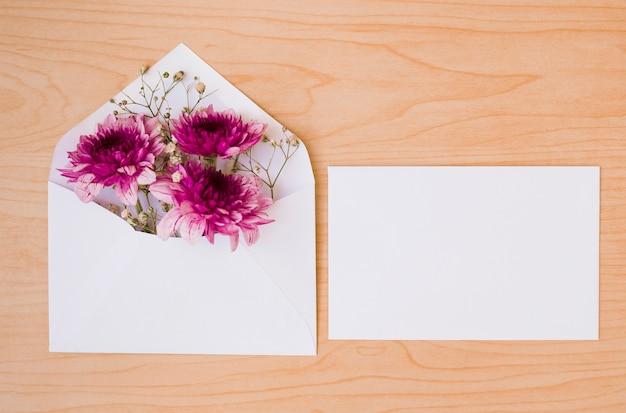 Enveloppe blanche avec fleurs et carte sur fond texturé en bois