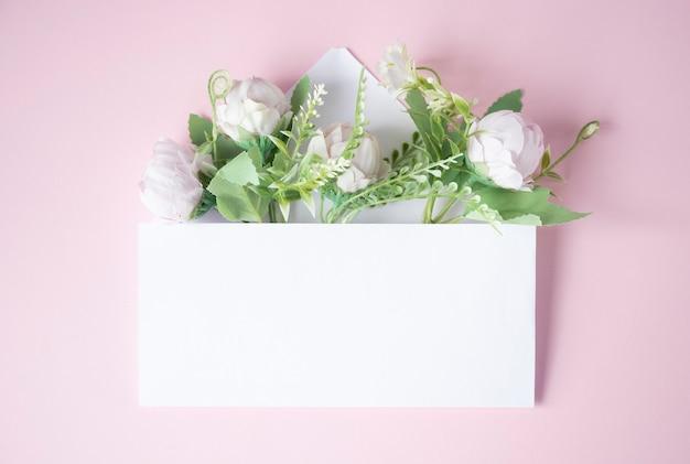 Enveloppe blanche avec des fleurs à l'intérieur sur fond rose clair