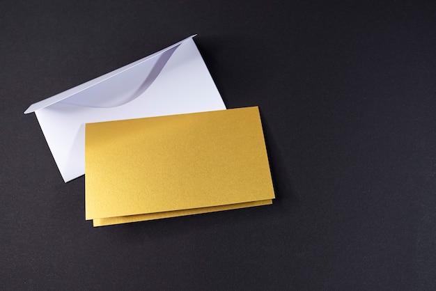 Enveloppe blanche et invitation comme carré doré avec surface vierge sur fond noir, maquette, espace pour le texte