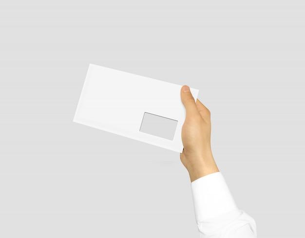 Enveloppe blanche vierge maquette tenant dans la main