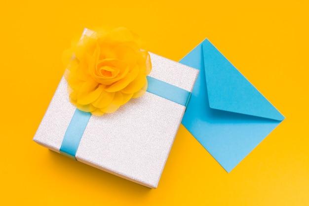 Une enveloppe bleue et une boîte-cadeau sur fond jaune, copiez l'espace, vue du dessus