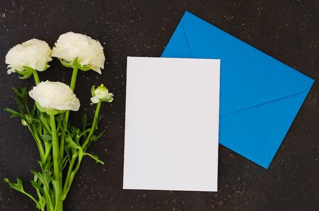 Enveloppe bleue avec du papier blanc vierge et bouquet de fleurs blanches