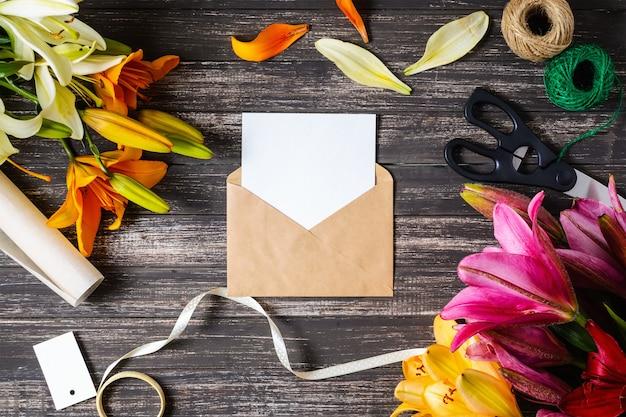 Enveloppe brune artisanale et feuille vide blanche avec des décorations sur fond en bois noir