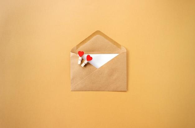 Une enveloppe brune avec des coeurs rouges dedans