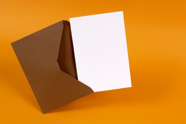Enveloppe brune avec lettre de message vide ou invitation isolée sur un fond d'or espace pour copie