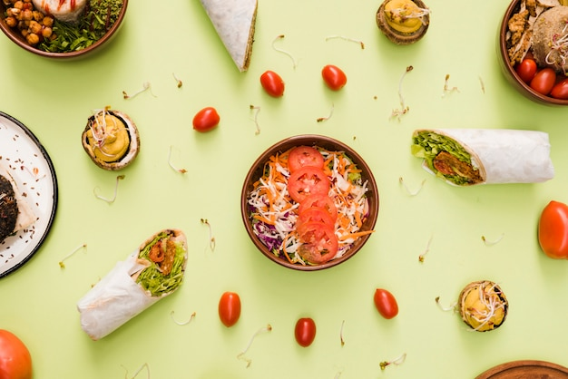 Enveloppe de burrito; tomates cerises et saladier sur fond vert menthe