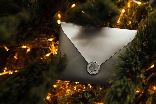 Enveloppe cadeau sur fond d'arbre de noël avec des guirlandes lumineuses