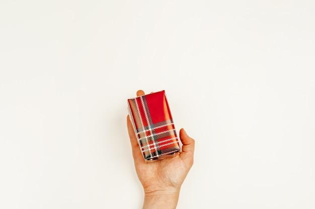 Enveloppé cadeau de noël dans les mains de la femme