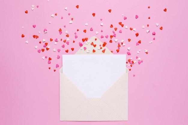 Enveloppe et carte avec coeurs roses et rouges sur rose