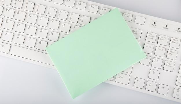 Enveloppe et clavier sur fond blanc, espace copie