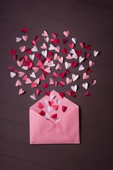 Enveloppe avec des coeurs en papier sur bois gris