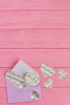 Enveloppe et cœurs en papier, vue de dessus.