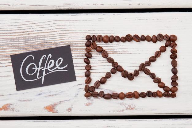 Enveloppe faite de grains de café sur bois blanc. concept de livraison de café.