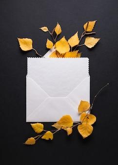 Enveloppe avec une félicitation sur fond noir. carte d'automne avec feuillage d'automne